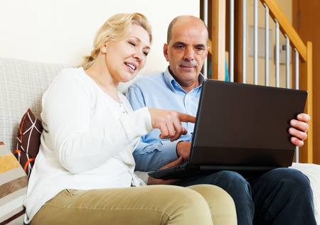 Happy mature couple with laptop at table at home Stock Photo