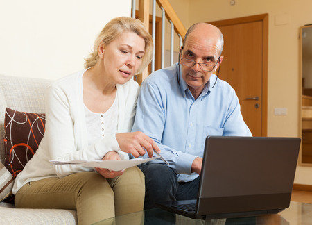 mature couple with documents and laptop in home interior  photo