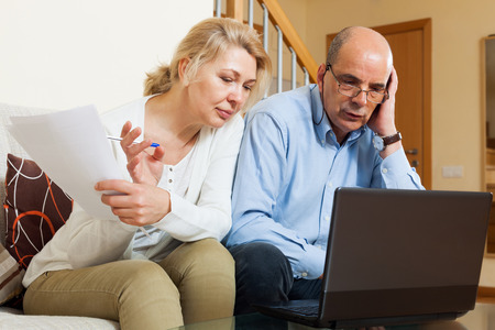 Serious mature man and woman with documents and laptop in home interior photo