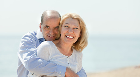 Happy elderly couple walking together on the beach in summer photo
