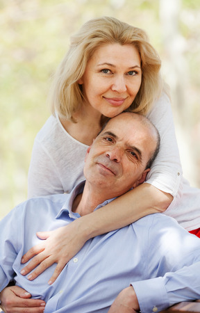 Happy senior man and mature woman together against blured trees of summer par Stock Photo