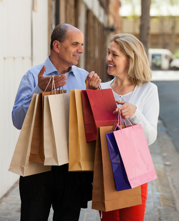 Smiling senior mature couple staying at street with purchases in hands photo