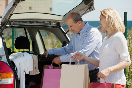 Smiling senior spouses with bags near car at shopping center parking lot  photo
