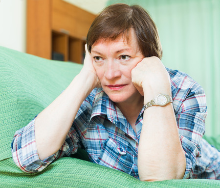 Portrait of sad senior woman having tough time and laying on couch photo