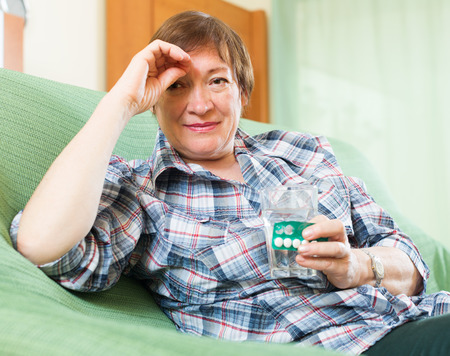 Tired mature woman sitting on sofa and holding glass of water and medicine photo