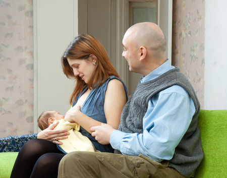 Mother breast feeding newborn baby at home interior. Father looks at the child  photo