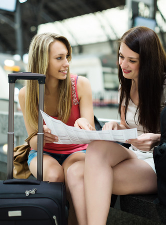 women with baggage and map waiting for train at station  photo