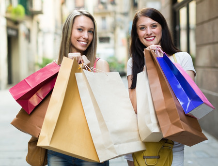 Two smiling female friends with shopping bags in the street  photo