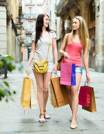 Two girls walking with shopping on city streets photo