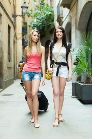 Two cheerful girls with luggage walking through city street photo