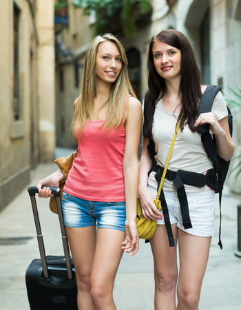Two happy girls with luggage walking through city street photo