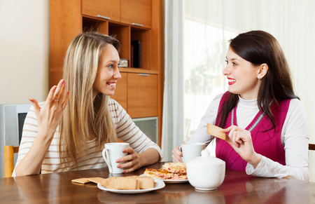 blabber: Two young women drinking tea with cookies in the kitchen Stock Photo