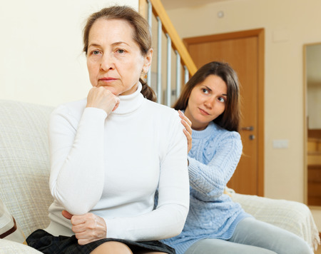 Teen girl tries reconcile with her mother in home. Focus on mature  photo