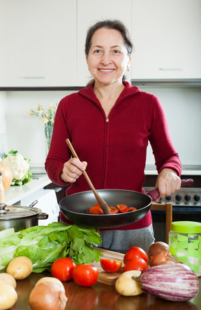 fryingpan:  mature housewife with frying-pan in home kitchen Stock Photo
