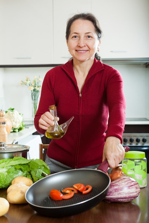 ordinary mature woman pouring oil to frying-pan at home photo