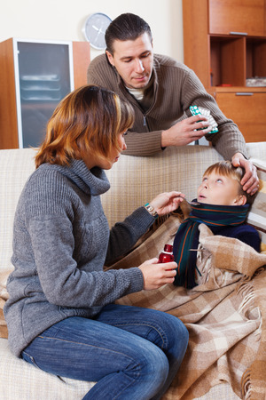 medicament: Parents giving  medicament to unwell  son at home Stock Photo