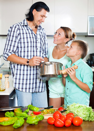 Happy man and woman with boy with fresh vegetables and greens in home kitchen photo