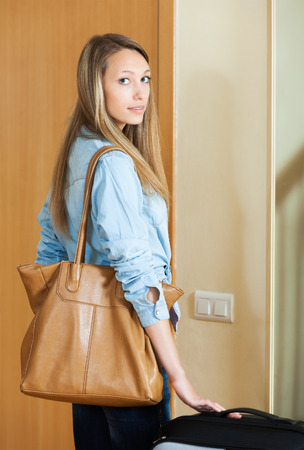 interphone: Attractive woman with luggage staying near door