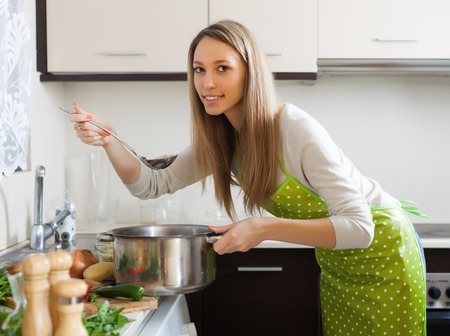 ordinary woman: Ordinary woman  in apron cooking  soup in kitchen