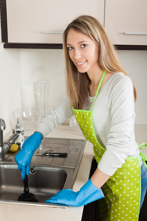 woman cleaning pipe with plunger in kitchen at home photo