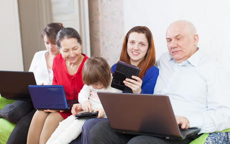 Happy family of with portable computers on sofa at home photo