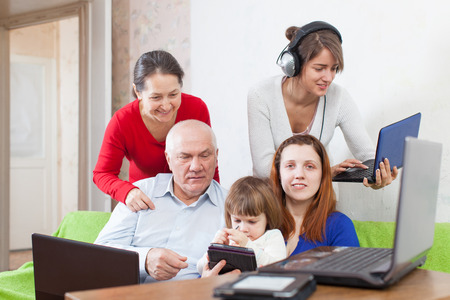 Group of people  uses few various electronic devices in home photo