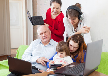 Happy multigeneration family uses  various electronic devices photo