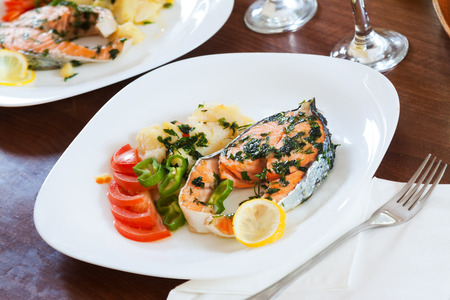 Grilled salmon fish in plate at table photo