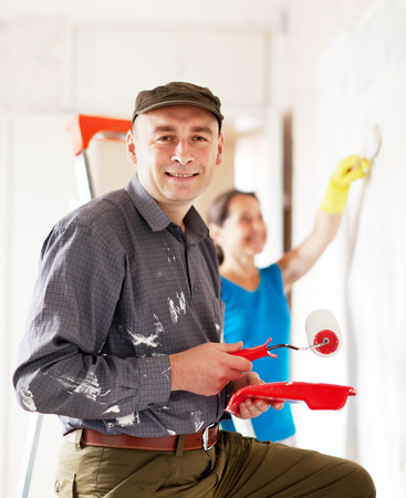 Man and woman paints wall at home together photo