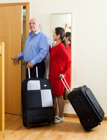 mature couple of travelers with suitcases in home going on holiday photo