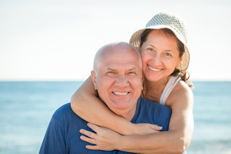 Portrait of mature couple against sea photo