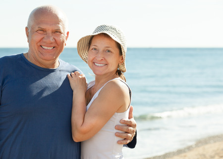Portrait of smiling mature couple together at sea vacation photo