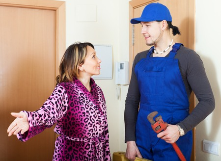 Smiling housewife meeting worker in uniform at home photo