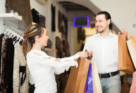 Happy couple with shopping bags at boutique photo