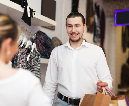 Happy couple  with shopping bags at clothing shop photo