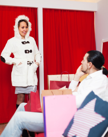 Ordinary couple trying coat in fitting-room. Focus on woman photo
