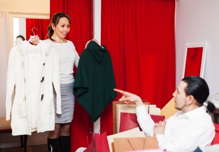 Couple choosing coat in fitting-room at clothing store photo