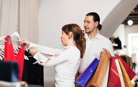 Woman and man with shopping bags choosing dress at boutique photo