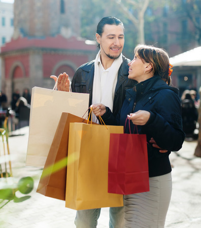 middle aged couple in black jackets with purchases at city street photo