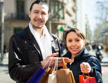 Positive couple with shopping bags at old european street photo