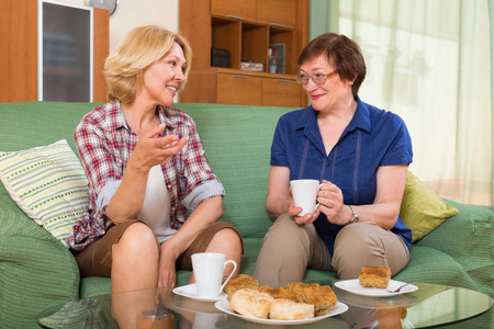2 50: Two positive mature women friends drinking tea and gossiping at home