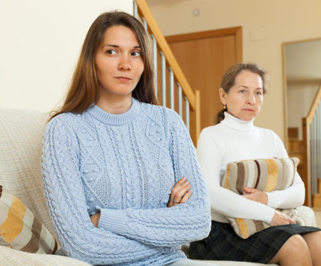 Mature mother and teen daughter sitting on sofa at home after conflict photo