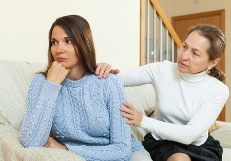 jeune fille adolescente: M�re et fille apr�s querelle sur le canap� � l'int�rieur de la maison