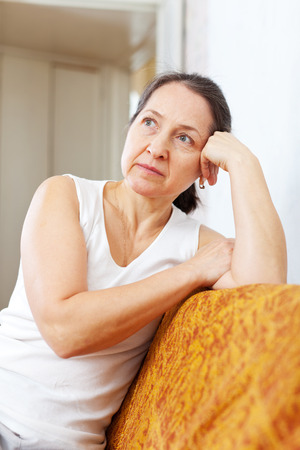 Portrait of pensive mature woman in home interior