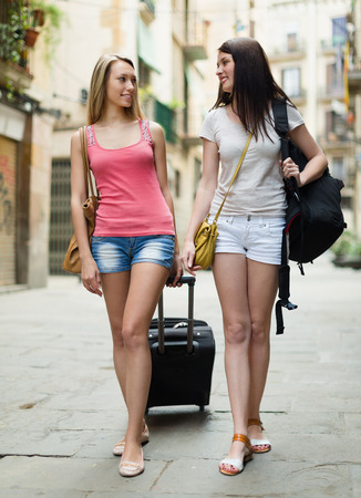 Two smiling girls with luggage walking through city street photo