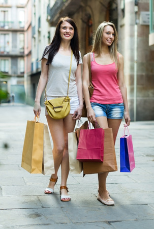 Smiling blonde and brunette with shopping bags walking by street photo