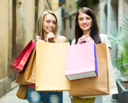 Two smiling young females walking by street with shopping bags in hands photo