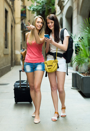 Two young girls smiling with baggage and heading to hotel on foot photo