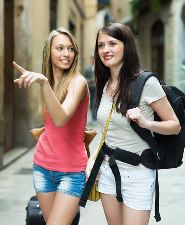 Two beautiful girls with luggage walking through city street photo