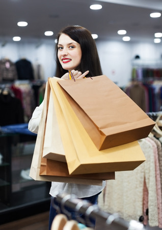 ordinary woman: Ordinary woman buyer with shopping bags at clothing store Stock Photo
